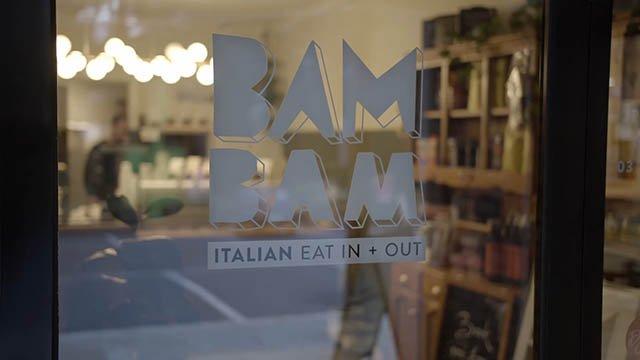 BAM BAM Italian logo printed on the glass front door of the restaurant